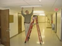 Man on a ladder fixing a ceiling tile
