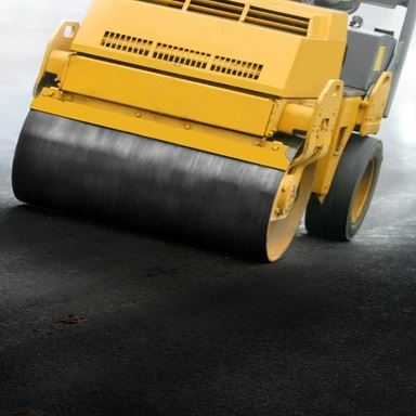 Rolling machine compacting asphalt pavement