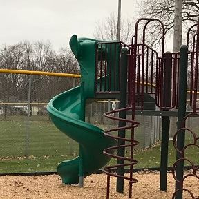 A slide attached to a play structure in a park.