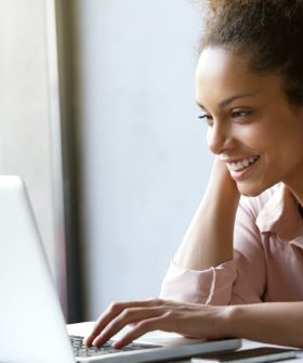 Woman smiling as she looks at her computer